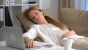 Empresaria cansada que duerme en el sofá en la oficina con el ordenador portátil y el teléfono almacen de video