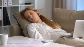 Empresaria cansada que duerme en el sofá en la oficina con el ordenador portátil y el teléfono almacen de metraje de vídeo