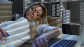 Empresaria cansada que duerme en el sofá en la oficina con el ordenador portátil y el teléfono en la noche almacen de metraje de vídeo