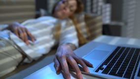 Empresaria cansada que duerme en el sofá en la oficina con el ordenador portátil y el teléfono en la noche almacen de video