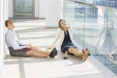 Empresaria cansada que se relaja en el vestíbulo de la oficina fotografía de archivo libre de regalías