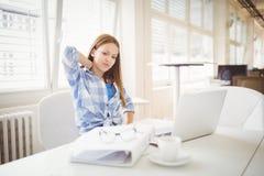 Empresaria cansada que se sienta en el escritorio en oficina creativa Fotografía de archivo