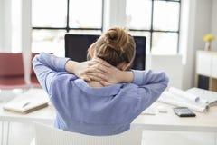 Empresaria cansada que sostiene su nuca imagenes de archivo