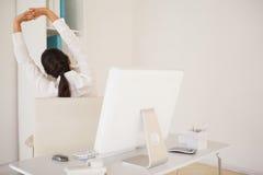 Empresaria casual que estira en su escritorio Foto de archivo libre de regalías