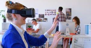 Empresaria caucásica bonita que usa las auriculares de la realidad virtual en la oficina moderna 4k almacen de video