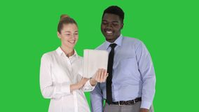 Empresaria caucásica joven y su colega africano que hacen la llamada video con la tableta en una pantalla verde, llave de la crom almacen de video