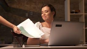 Empresaria caucásica linda que toma documentos del otro trabajador con gratitud mientras que se sienta en su ordenador y sonrisa metrajes