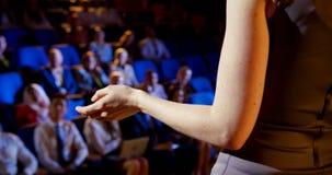 Empresaria caucásica que habla en seminario del negocio sobre etapa en el auditorio 4k almacen de metraje de vídeo
