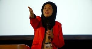 Empresaria cauc?sica madura del hijab que habla en el podio en el auditorio 4k metrajes