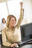 Empresaria Celebrating Success While que usa el ordenador en el escritorio Imagen de archivo libre de regalías