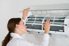 Empresaria Checking Air Conditioner imagenes de archivo