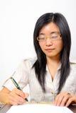Empresaria china, sentándose en la escritura del escritorio imágenes de archivo libres de regalías