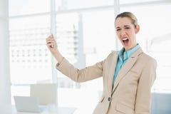Empresaria chocada linda que sostiene su smartphone que mira la cámara Fotografía de archivo