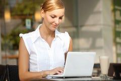 Empresaria con café y la computadora portátil Imagen de archivo