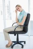 Empresaria con clase agotada que se sienta en su silla de eslabón giratorio Foto de archivo