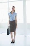 Empresaria con clase atractiva que presenta sosteniendo una cartera Imagen de archivo