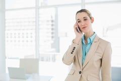 Empresaria con clase concentrada que llama por teléfono con su smartphone Fotos de archivo