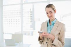 Empresaria con clase contenta que manda un SMS con su smartphone Fotos de archivo libres de regalías