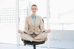 Empresaria con clase contenta que se sienta en la posición de loto respecto a su silla de eslabón giratorio Foto de archivo