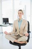 Empresaria con clase preciosa que medita en la posición de loto respecto a su silla de eslabón giratorio Imagen de archivo