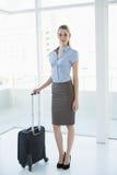 Empresaria con clase que plantea la colocación en la oficina que sostiene una maleta Imágenes de archivo libres de regalías