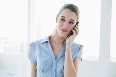 Empresaria con clase sonriente que llama por teléfono con su smartphone Imágenes de archivo libres de regalías