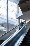 Empresaria con el bolso negro grande y el teléfono móvil que ascienden en la escalera móvil Fotografía de archivo