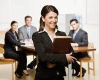 Empresaria con el cuaderno y los compañeros de trabajo Imagenes de archivo