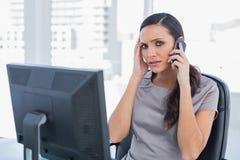 Empresaria con el dolor de cabeza que tiene una conversación telefónica Imagen de archivo