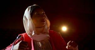 Empresaria con el hijab que habla en seminario del negocio en el auditorio 4k almacen de metraje de vídeo