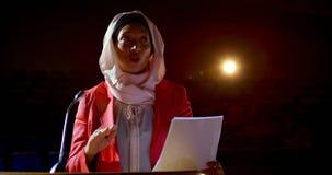 Empresaria con el hijab que habla en seminario del negocio en el auditorio 4k metrajes