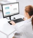 Empresaria con el mensajero en el ordenador en la oficina Imagen de archivo libre de regalías