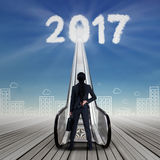 Empresaria con el número 2017 y la escalera móvil Imagenes de archivo