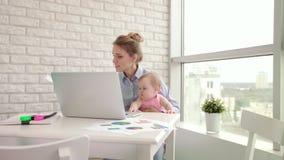 Empresaria con el niño que trabaja con los documentos Freelancer en el permiso por maternidad almacen de metraje de vídeo