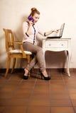 Empresaria con el ordenador portátil de la pantalla táctil del teléfono Imagen de archivo libre de regalías
