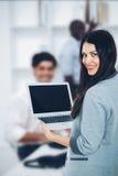 Empresaria con el ordenador portátil en oficina Imágenes de archivo libres de regalías
