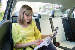 Empresaria con el ordenador portátil en coche Imagenes de archivo