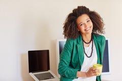 Empresaria con el pelo rizado que sostiene una taza de café imagen de archivo libre de regalías