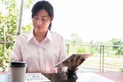 Empresaria con el sitt del gráfico de la tableta digital y del resumen financiero fotografía de archivo libre de regalías
