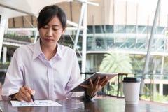 Empresaria con el sitt del gráfico de la tableta digital y del resumen financiero imagenes de archivo