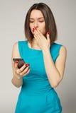 Empresaria con el smartphone que recibe noticias impactantes Fotografía de archivo libre de regalías
