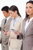 Empresaria con el teléfono móvil al lado de colegas Imagen de archivo libre de regalías