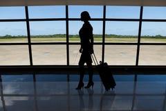 Empresaria con equipaje que camina contra ventana del aeropuerto fotos de archivo