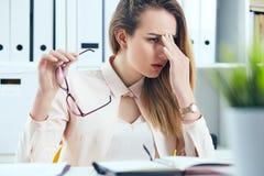 Empresaria con exceso de trabajo cansada en vidrios en la oficina que cubre su cara con la mano Foto de archivo libre de regalías