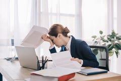 empresaria con exceso de trabajo en traje con los papeles en manos en el lugar de trabajo Foto de archivo