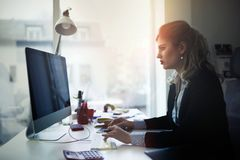 Empresaria con exceso de trabajo que permanece adentro tarde Imagenes de archivo