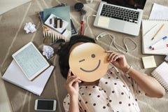 Empresaria con la cara sonriente en manos imagenes de archivo