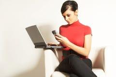 Empresaria con la computadora portátil y el teléfono Imagen de archivo libre de regalías