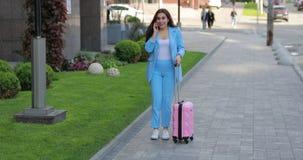 Empresaria con la maleta que habla por el teléfono en ciudad y tener buenas noticias almacen de metraje de vídeo