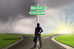 Empresaria con la señal de tráfico a las finanzas de la recuperación o de la recesión Fotografía de archivo libre de regalías